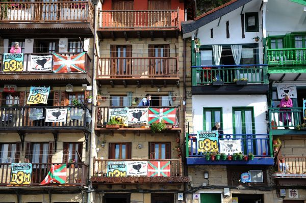 People listen to a pre-electoral meeting from balconies adorned with Basque flags and posters in support of the pro-Basque independence party Democracia Tres Millones (D3M) in Pasajes San Juan February 5, 2009