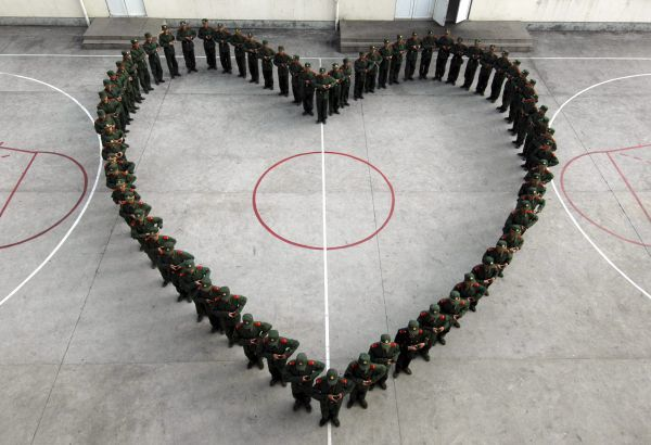 Paramilitary recruits form a heart shape on a basketball court during a media event in Wenzhou, Zhejiang province February 12, 2009, to celebrate Valentine's Day. In a sign of the increasing influence of Western customs on Chinese culture