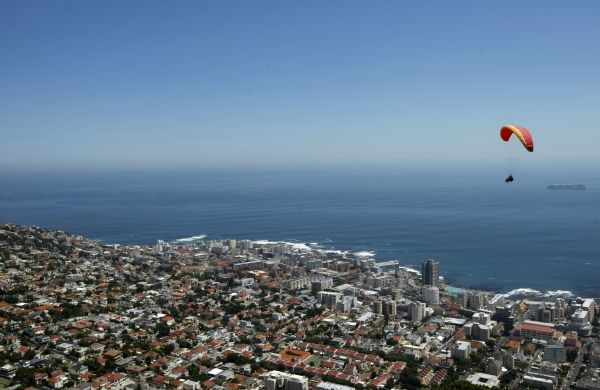 A paraglider takes advantage of windless warm conditions as he rides thermals above Cape Town's Sea Point beach front March 1, 2009. REUTERS/Mike Hutchings (SOUTH AFRICA)