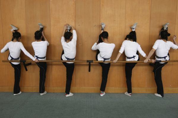 Students stretch against a wall during physical practice for Yueju opera at an art school in Hangzhou, Zhejiang province March 16, 2009. Also known as Shaoxing opera, this variant emerged in the early 1900s in the eastern city of Shaoxing, Zhejiang Province