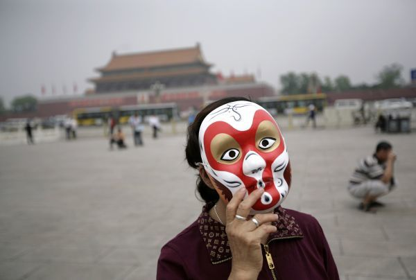 A woman wears a mask depicting Sun Wukong, also known as the Monkey King, on Beijing's Tiananmen Square June 17, 2009. REUTERS/Jason Lee (CHINA SOCIETY IMAGES OF THE DAY)