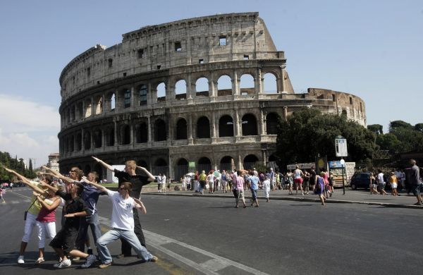 A group of young people pose in front of the Coliseum of Rome, Italy, August 16, 2009. REUTERS/Hazir Reka (ITALY TRAVEL)