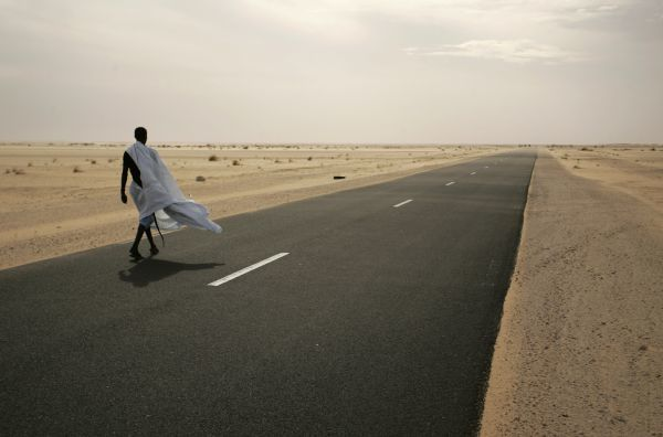 A man walks on the road between Nouahibou and Nouakchott, where three Spanish aid workers were abducted from, December 3, 2009