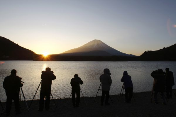 People take pictures of the sunrise appearing from the foot of Japan's highest mountain, Mount Fuji, in Fujikawaguchiko town, southwest of Tokyo December 31, 2009
