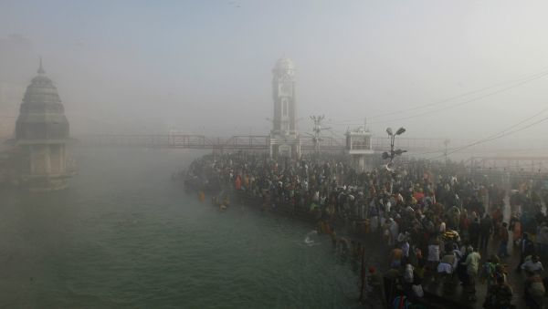 "Hindu devotees pray on the banks of river Ganges amidst heavy fog during the ""Kumbh Mela"" or the Pitcher Festival, in the northern Indian town of Haridwar January 15, 2010"