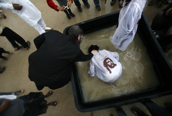 A Greek Orthodox priest dunks a pilgrim in water from the Jordan River during a ceremony at the baptismal site known as Qasr el-Yahud on the banks of the Jordan River near the West Bank city of Jericho January 18, 2010