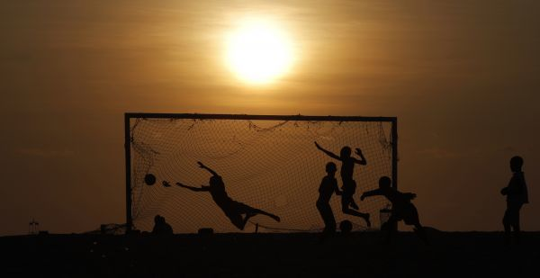 Angolan youths play soccer on a beach in the capital Luanda January 23, 2010. REUTERS/Mike Hutchings (ANGOLA - Tags: SPORT SOCCER IMAGES OF THE DAY SOCIETY)