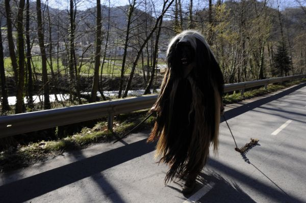 A villager wearing a carnival costume walks on the road during celebrations in the Navarran village of Zubieta February 2, 2010