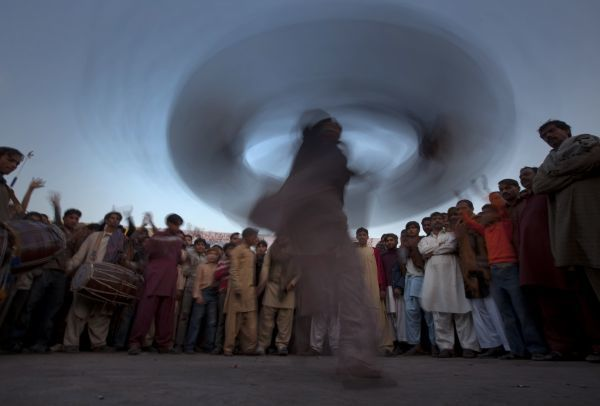 Revellers watch as a devotee plays and dances with multiple drums outside the mausoleum of Data Ganj Bakhsh during a three-day festival commemorating the Sufi saint's death anniversary in Lahore February 4, 2010. REUTERS/Adrees Latif (PAKISTAN - Tags
