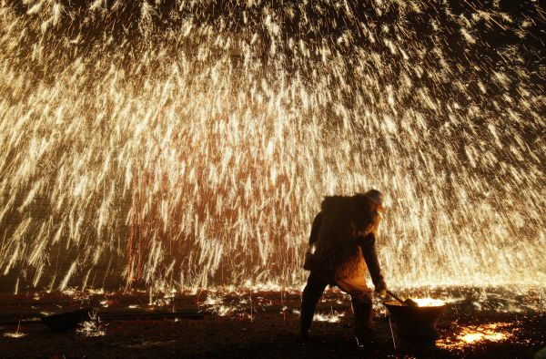 A traditional performer sprays molten iron against a concrete wall to celebrate the Lantern Festival in Nuanquan town of Yuxian County, Hebei province, February 27, 2010