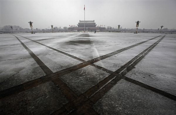 Tire tracks are seen across a light covering of snow on Tiananmen Square in Beijing March 14, 2010. The square was cordoned off to the public due to the closing session of the National People's Congress (NPC) at the adjacent Great Hall of the People