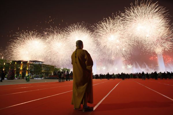 A Buddhist monk watches fireworks during the opening ceremony of the Shanghai World Expo in Shanghai April 30, 2010. REUTERS/Aly Song (CHINA - Tags: BUSINESS POLITICS RELIGION IMAGES OF THE DAY)
