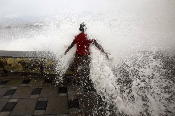 A boy is hit by a large wave during high tide at Mumbai's seafront June 14, 2010. REUTERS/Danish Siddiqui (INDIA - Tags: ENVIRONMENT SOCIETY IMAGES OF THE DAY)