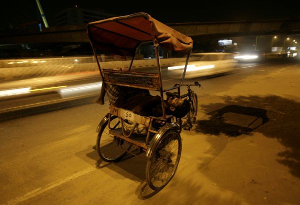 A cycle rickshaw puller sleeps along a busy road in New Delhi June 30, 2010. REUTERS/Mukesh Gupta (INDIA - Tags: SOCIETY)