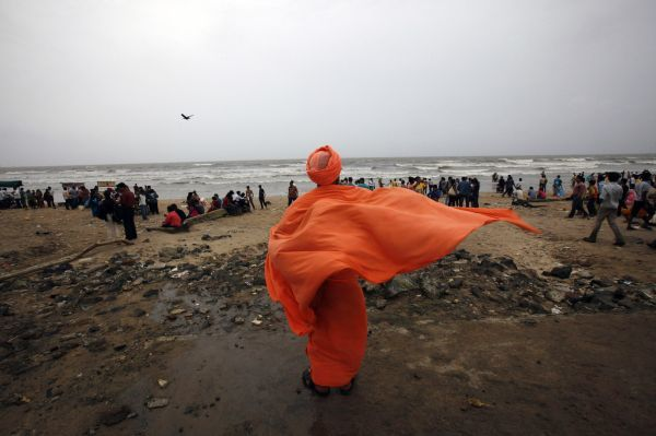 A Hindu priest dries his stole on a beach as it drizzles in Mumbai August 1, 2010. REUTERS/Danish Siddiqui (INDIA - Tags: RELIGION SOCIETY)