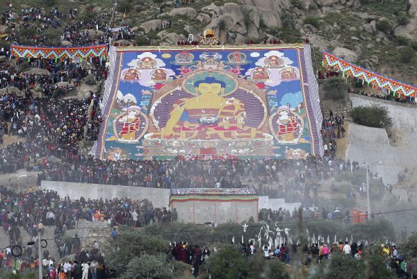Tibetan Buddhists and tourists view a huge Tangka, a religious silk embroidery or painting unique to Tibet, during the Shoton Festival at Drepung Monastery on the outskirts of Lhasa, Tibet Autonomous Region August 10, 2010. Picture taken August 10, 2010