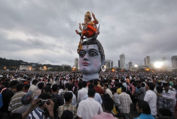 "Devotees watch idols of the Hindu elephant god Ganesh, the deity of prosperity and Lord Shiva as they are placed on the seashore before immersion on the last day of ""Ganesh Chaturthi"", in Mumbai September 22, 2010"