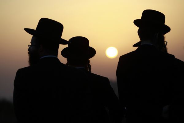 Ultra-Orthodox Jewish men stand together after crossing into Jerusalem through an Israeli checkpoint after praying at Rachel's Tomb in the West Bank town of Bethlehem October 19, 2010