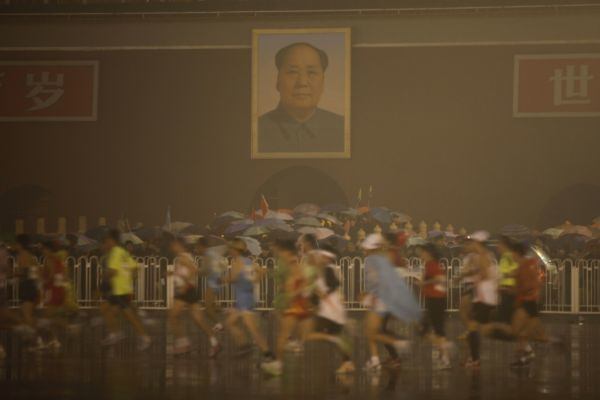 Participants run past the Tiananmen Gate in front of the portrait of late Chinese leader Mao Zedong during the 2010 Beijing Marathon on a rainy day in Beijing October 24, 2010. REUTERS/Grace Liang (CHINA - Tags: SPORT ATHLETICS ENVIRONMENT)