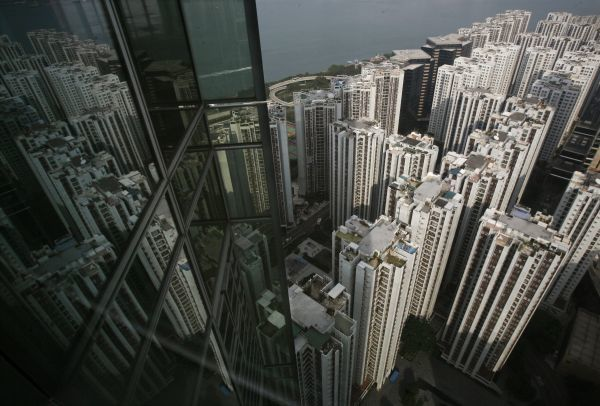 Residential blocks are reflected on the glass panes of a business tower in Hong Kong November 3, 2010