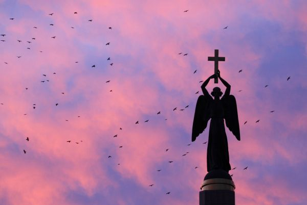 Birds fly near a statue of an angel holding a cross, the symbol of the city, at sunset in Stavropol November 5, 2010. REUTERS/Eduard Korniyenko (RUSSIA - Tags: RELIGION ANIMALS)