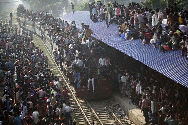 An overcrowded train approaches as other passengers wait to board at a railway station in Dhaka, November 16, 2010