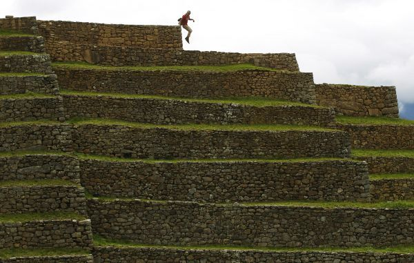 A tourist jumps from a terrace at the Inca citadel of Machu Picchu in Cuzco December 2, 2010