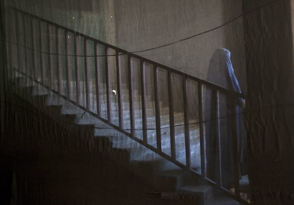 A photograph taken from behind a curtain shows an Afghan Shi'ite Muslim woman clad in burqa stand at the entrance of Chendawol mosque during a Muharram procession to mark Ashura in Kabul December 13, 2010