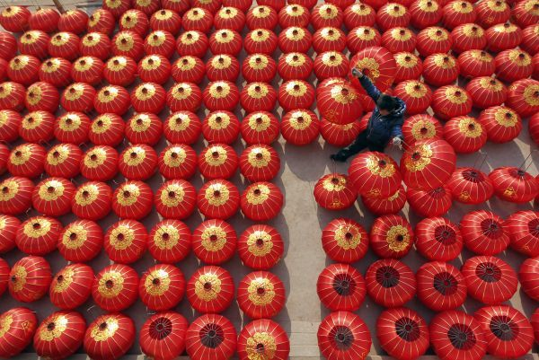 A worker lays out newly made red lanterns to dry at a lantern factory in Jishan county, Shanxi province December 27, 2010. The lanterns are being prepared for New Year celebrations and the coming Chinese Lunar New Year, which falls on February 3, 2011