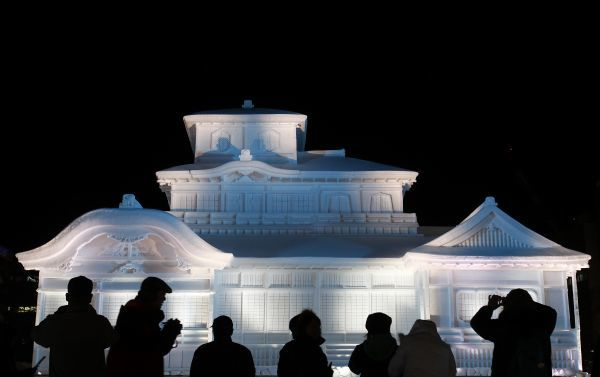 "Visitors look at an illuminated snow sculpture of Japan's national treasure ""Hiunkaku of Hongwanji"" at the 62nd Sapporo snow festival in Sapporo, on Japan's northern island of Hokkaido February 7, 2011"