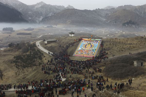 Tibetan Buddhists and tourists view a giant Thangka, a religious silk embroidery or painting, displayed on a hill near the Langmu Temple in Gannan Tibetan Autonomous Prefecture, Gansu province February 15, 2011