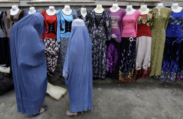 Afghan women shop for clothes hung on mannequin displays along a street in Kabul March 29, 2011. REUTERS/Omar Sobhani (AFGHANISTAN - Tags: SOCIETY)
