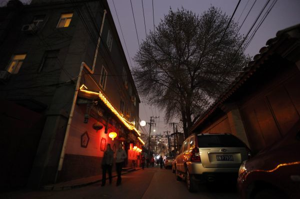 People walk along a traditional alleyway, or hutong, in central Beijing April 5, 2011