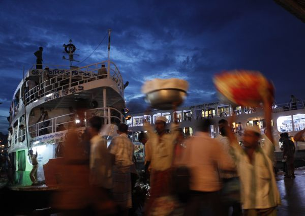 People board passenger boats as they leave ahead of the Muslim Eid al-Fitr holiday during dusk at Sadarghat in Dhaka August 25, 2011. REUTERS/Andrew Biraj (BANGLADESH - Tags: RELIGION TRANSPORT)