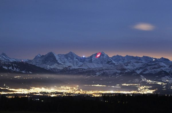 A giant light installation of the flag of Switzerland, by Swiss artist Gerry Hofstetter, illuminates the north face of the Jungfrau mountain, next to the Eiger and Moench mountains (L) and above the city of Thun (bottom), as seen from Oberbuetschel