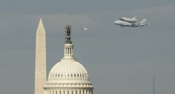 Space Shuttle Discovery flies past the Washington Monument and the U