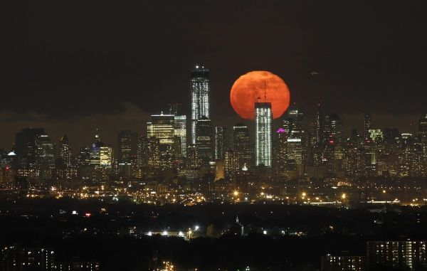 A full moon as seen from West Orange, New Jersey, rises over the skyline of Lower Manhattan and One World Trade Center (L) in New York, May 6, 2012. REUTERS/Gary Hershorn (UNITED STATES - Tags: CITYSPACE ENVIRONMENT SOCIETY)