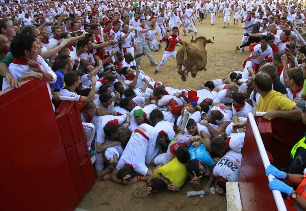 A fighting cow leaps over revellers upon entering the bullring following the first running of the bulls of the San Fermin festival in Pamplona July 7, 2013. Several runners suffered light injuries in a run that lasted four minutes and six seconds