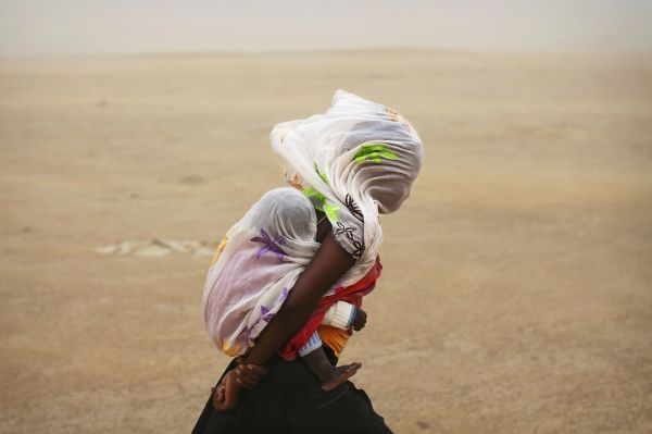 A woman carrying her baby and wrapped with a shawl walks through a sandstorm in Timbuktu July 29, 2013. REUTERS/Joe Penney (MALI - Tags: SOCIETY ENVIRONMENT TPX IMAGES OF THE DAY) FOR BEST QUALITY IMAGE ALSO SEE: GM1E9AB18FD01 - RTX124D6