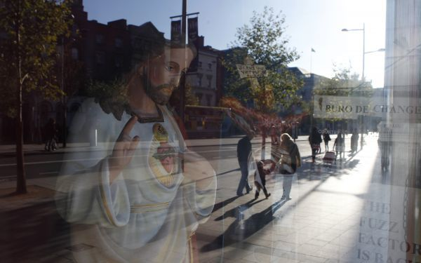 Pedestrians are reflected in the window of a shop selling religious goods on O'Connell streetin central Dublin November 14, 2010