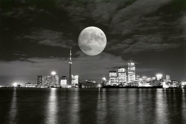 A full moon makes its way over the Toronto skyline, September 16, 1986 as the lights from buildings reflect off Lake Ontario