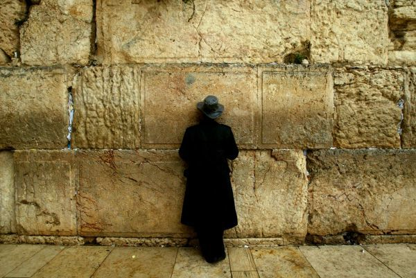 An Ultra Orthodox Jewish man prays at the Western Wall (Wailing Wall) during a rainstorm January 3, 2003