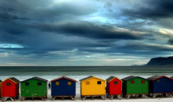 A lone stroller stares out to sea beyond a row of beach huts as a cold front sets in over Muizenberg in Cape Town, August 12, 2003. NO RIGHTS CLEARANCES OR PERMISSIONS ARE REQUIRED FOR THIS IMAGE REUTERS/Mike Hutchings MH/SN Also see GF2DVKWFJKAA