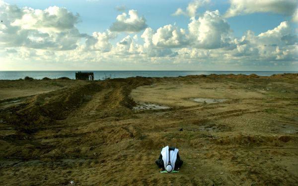 A PALESTINIAN MAN PRAYS TO ALLAH AT A ROADSIDE LEADING TO KHAN YOUNIS ALONG THE MEDITERRANEAN SEA NEAR THEJEWISH SETTLEMENT OF NETZARIM