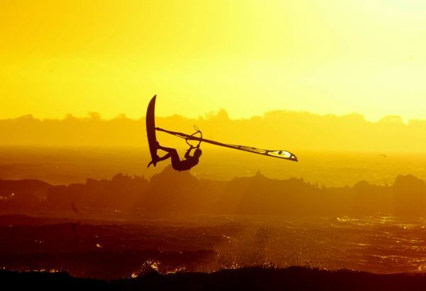 A windsurfer gets airbourne as the sun sets over Cape Town's Blaauwberg beach, February 23, 2004. Strong south easterly winds and clear summer days draws thousands of tourists and local enthusiasts of the sport to the city's beaches every year