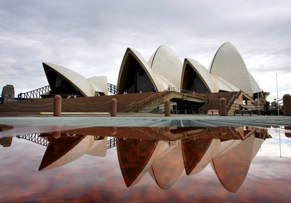 "Sydney's landmark Opera House is reflected in a pool of rain water March 31, 2005. The roof, or ""sails"" as they are referred to, were described by Jorn Utzon, the Danish Architect who designed them, as standing out ""like a big exotic bird&quot"