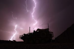 An armoured vehicle is framed by a bolt of lightning during a storm at Combat Outpost